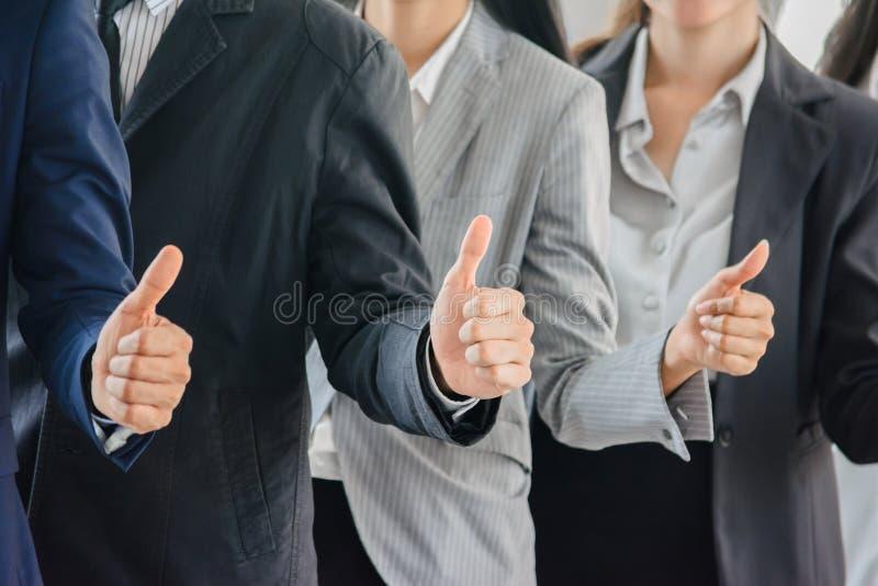 Polegares ginving do homem de negócio e da equipe de mulher acima imagens de stock