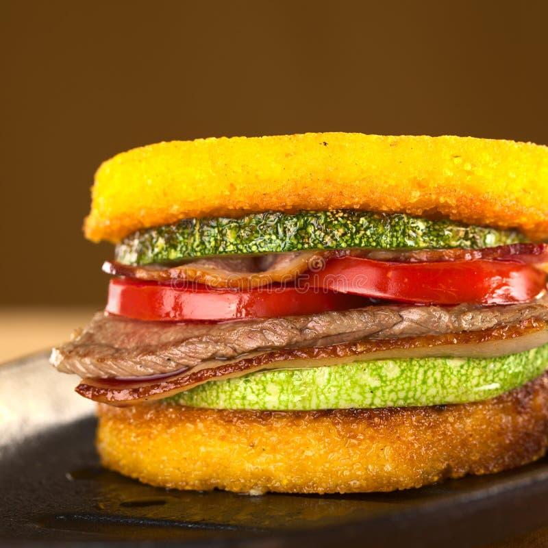 Polemta汉堡用牛肉、夏南瓜、蕃茄和烟肉 免版税图库摄影