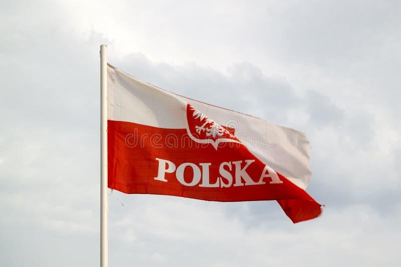 Polen flagga p? en bl? himmel med molnbakgrund royaltyfria bilder