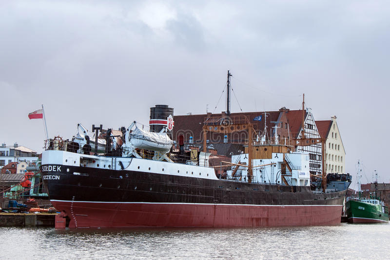 POLEN GDANSK - DECEMBER 18, 2011: Sikt av denmuseum fraktbåten Soldek nära historiska byggnader av ön Olowianka royaltyfria foton