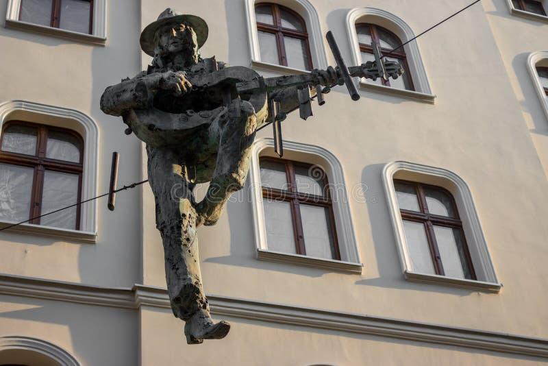 Polen, Katowice - 12/06/2018: Statuenmann mit giutar und Hut auf Draht gegen Gebäude lizenzfreies stockbild