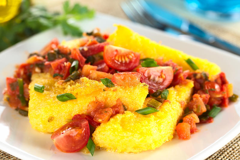 Polenta with Hogao. Polenta slices with Hogao, also called Criollo Sauce, which is a Colombian sauce made of tomato, onion and cilantro (Selective Focus, Focus royalty free stock photos