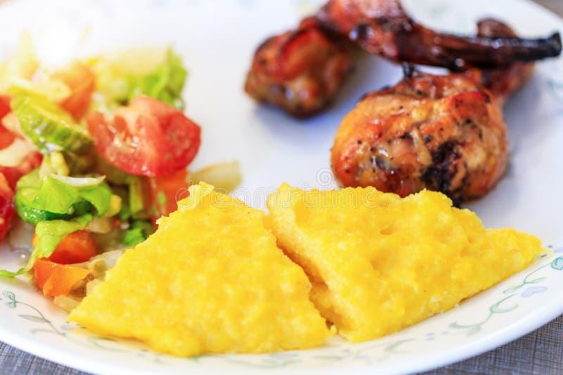 Polenta of Mamaliga, gebakken kippenbenen en salade in buitensporige plaat Traditioneel voedsel en culinaire cultuur specifiek vo royalty-vrije stock foto