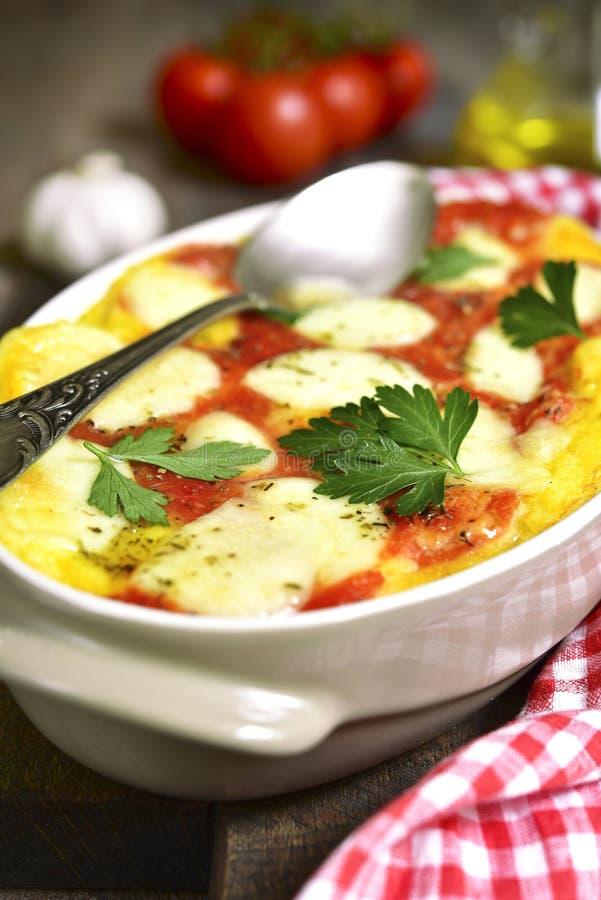 Polenta met tomaat en kaas wordt gebakken die royalty-vrije stock fotografie