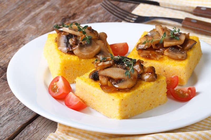Polenta mit Pilzen, Tomaten und Thymian auf dem Tisch stockfoto