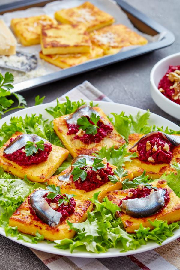 Polenta Squares with beetroot and anchovies stock photography