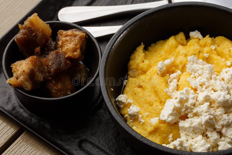 Polenta ucraina tipica del piatto - Banosh con formaggio e lardo Cucina ucraina porridge del mais con bacon, cotenne grigliate immagine stock