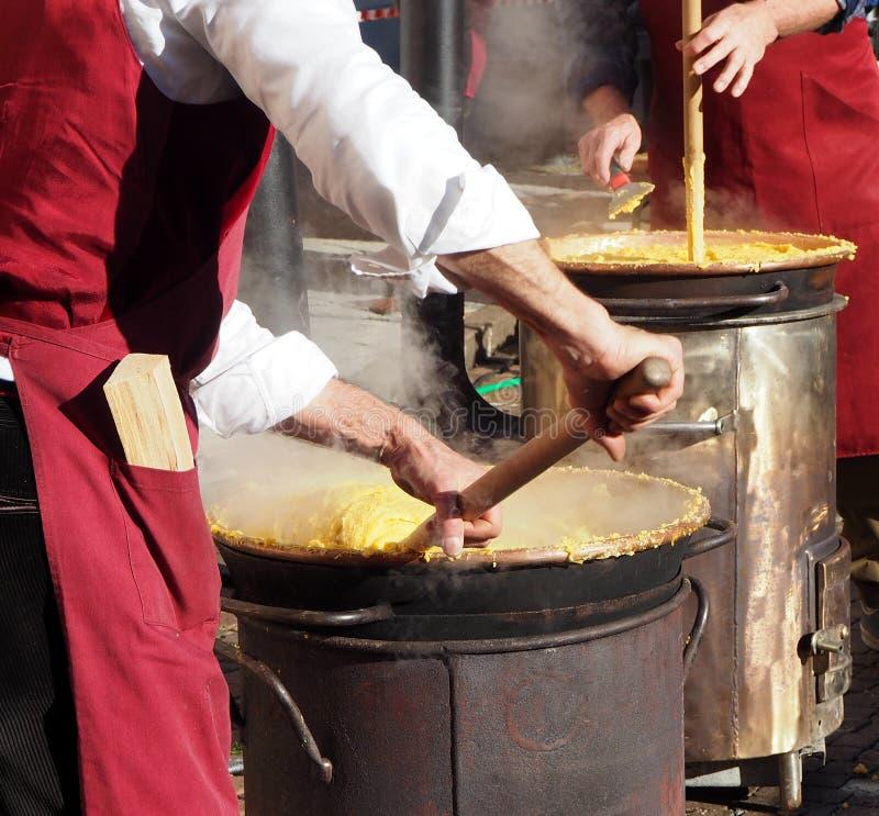 Polenta van de twee chef-kokkok op de traditionele manier van noordoostelijk Italië op kleine houten-in brand gestoken kooktoeste stock afbeeldingen