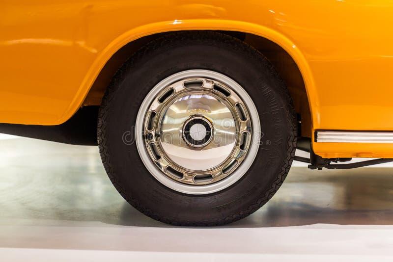 Polerad bilkant med det svarta tappninghjulet på den orange bilen arkivbilder