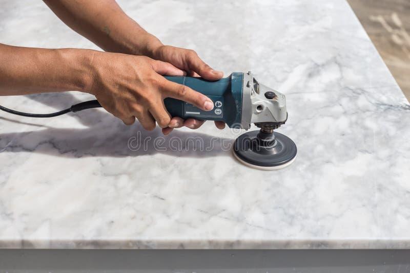Polerande marmortabell för man med vinkelmolar royaltyfri foto
