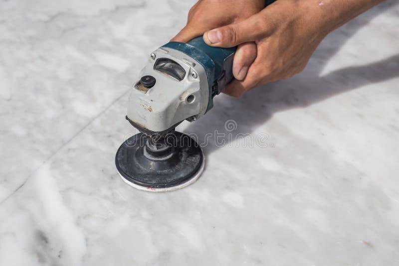 Polerande marmortabell för man med vinkelmolar royaltyfria foton