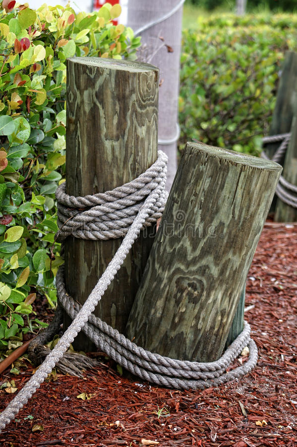 Poles with rope. Wooden poles are mounted in the ground and tied together with rope making for a nautical type fencing or boundary on an overcast day stock photo