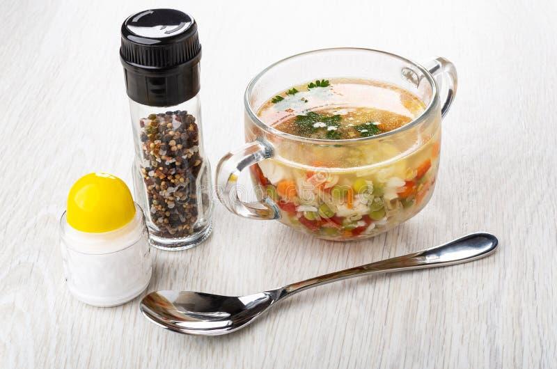 Polewka z kurczaka mięsem, ryż, warzywa w szklanym przejrzystym pucharze, sól, słój z condiment, łyżka na drewnianym stole obrazy stock