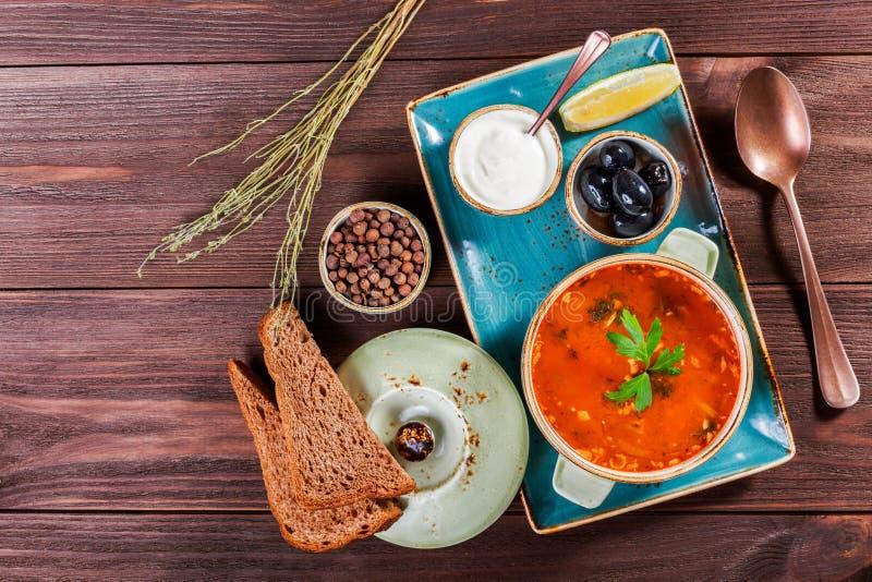 Polewka z mięsem, oliwkami, ziele, cytryną, kwaśną śmietanką w pucharze, czarnym chlebem i pikantność na ciemnym drewnianym tle,  zdjęcie stock