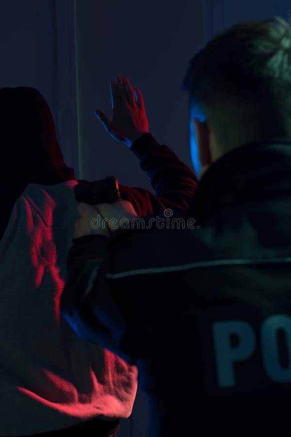 Poli que señala la arma de mano en el delincuente foto de archivo libre de regalías