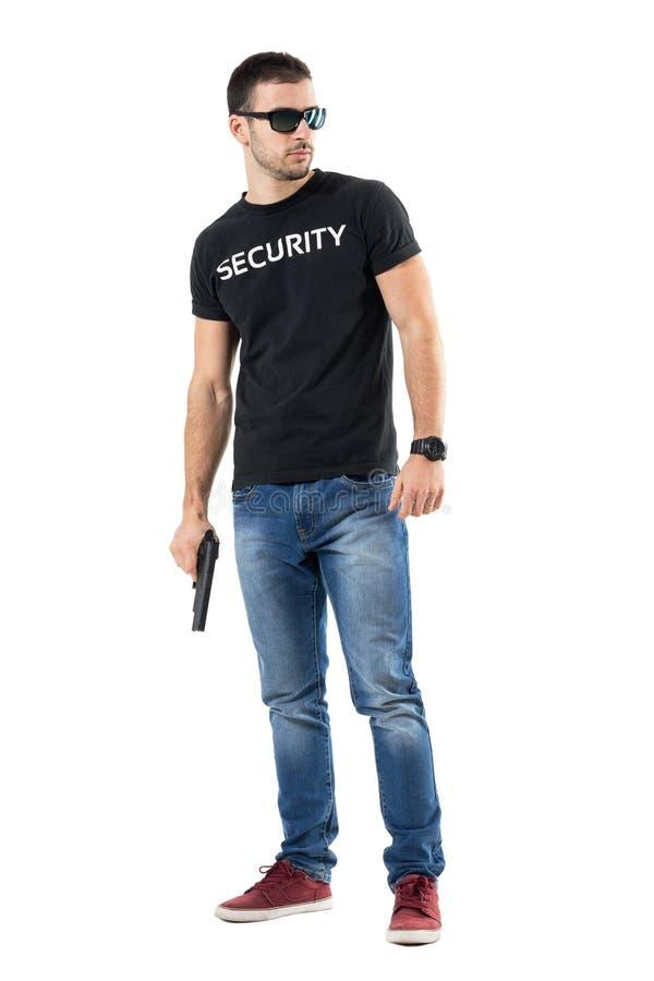 Poli secreto joven prudente con las gafas de sol que sostienen el arma que mira lejos fotos de archivo