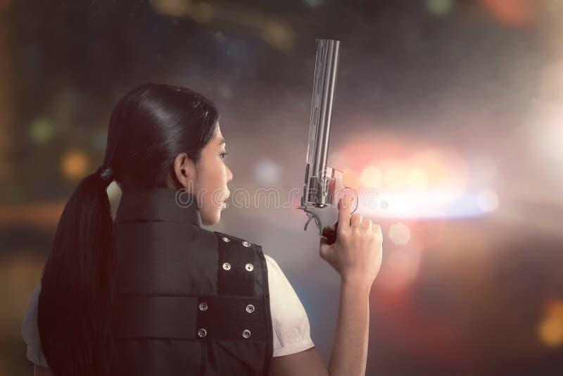 Policía asiática atractiva de la mujer con el uniforme con armas imagenes de archivo