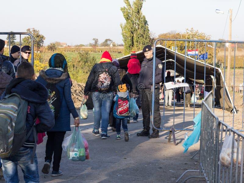 Policía croata que mira a los refugiados, principalmente niños, cruzando la frontera de Serbia Croacia en Berkasovo Bapska fotos de archivo
