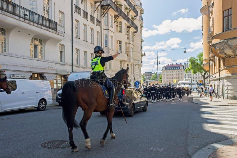 Policía del caballo con la banda sueca del ejército en la calle en Estocolmo imagen de archivo libre de regalías