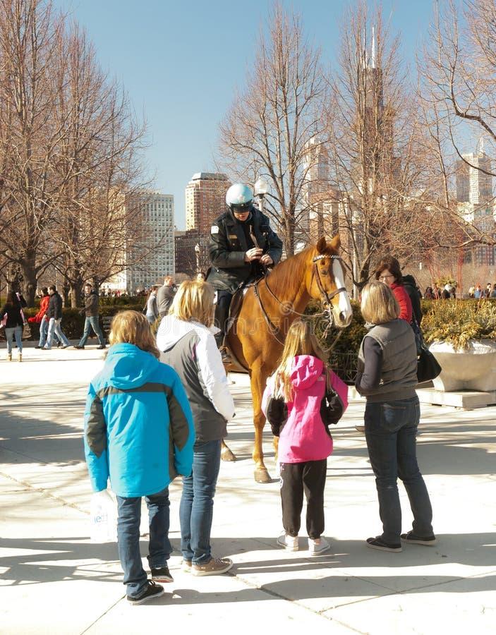 Policía en el caballo que habla con los niños foto de archivo libre de regalías