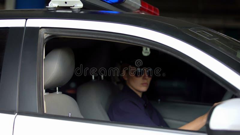 Policía femenina que conduce el coche policía, leyes el patrullar del tráfico, supervisando orden imagen de archivo libre de regalías