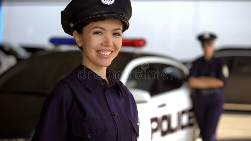 Policía hermosa que sonríe cerca del coche policía, anuncio de la academia de policía imagen de archivo
