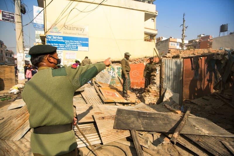 Policía nepalesa desconocida durante una operación en la demolición de los tugurios residenciales foto de archivo