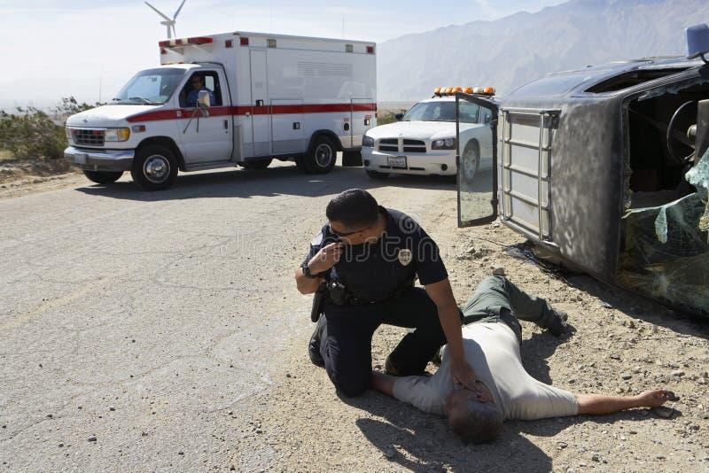 Policía que comprueba el pulso de la víctima de choque de coche foto de archivo
