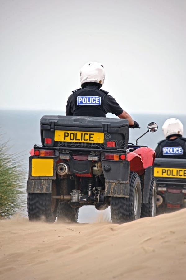 Policía que patrulla en las bicis del patio en las arenas de Formby, Reino Unido foto de archivo libre de regalías