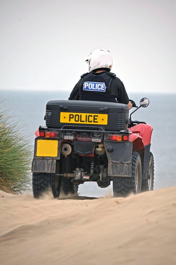 Policía que patrulla en las bicis del patio en las arenas de Formby, Reino Unido imagen de archivo