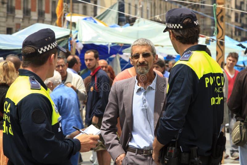 Policía que pregunta a un hombre imagenes de archivo