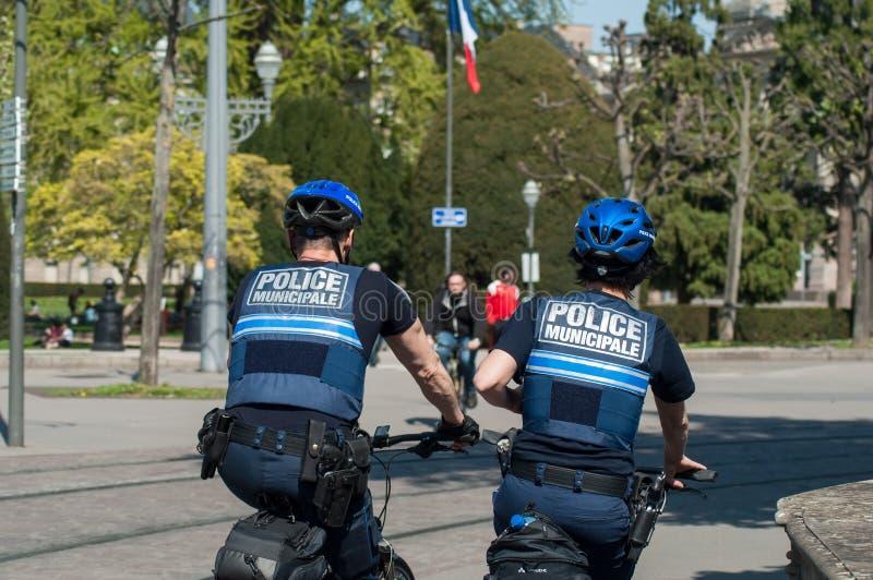 Policías municipales en la bici de montaña en patrullar en la calle imagen de archivo