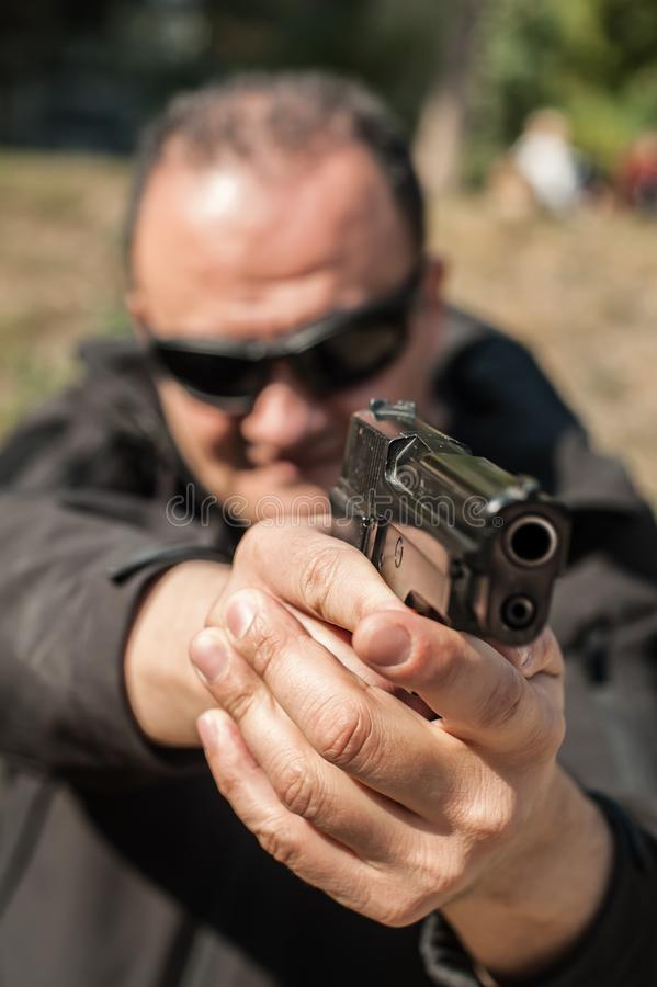 Police agent and bodyguard pointing pistol to protect from attacker royalty free stock photos