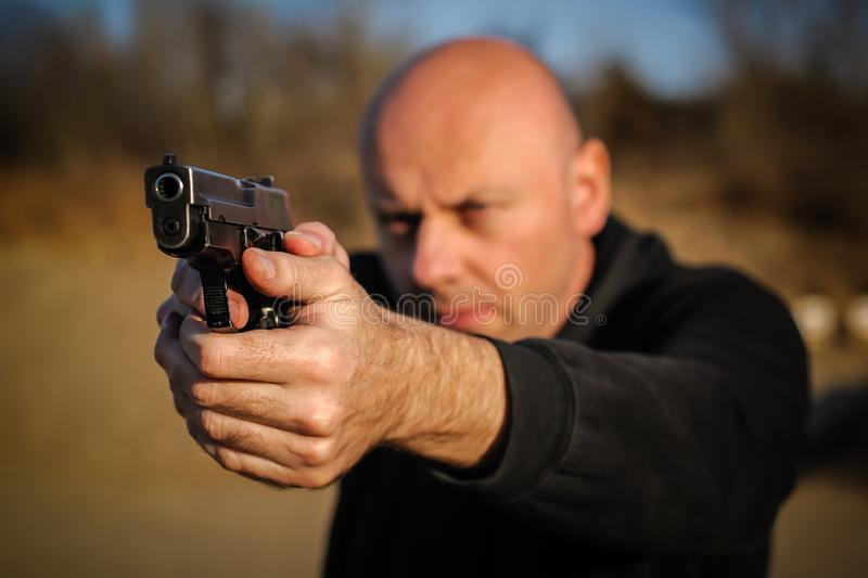 Police agent and bodyguard pointing pistol to protect from attacker royalty free stock photography