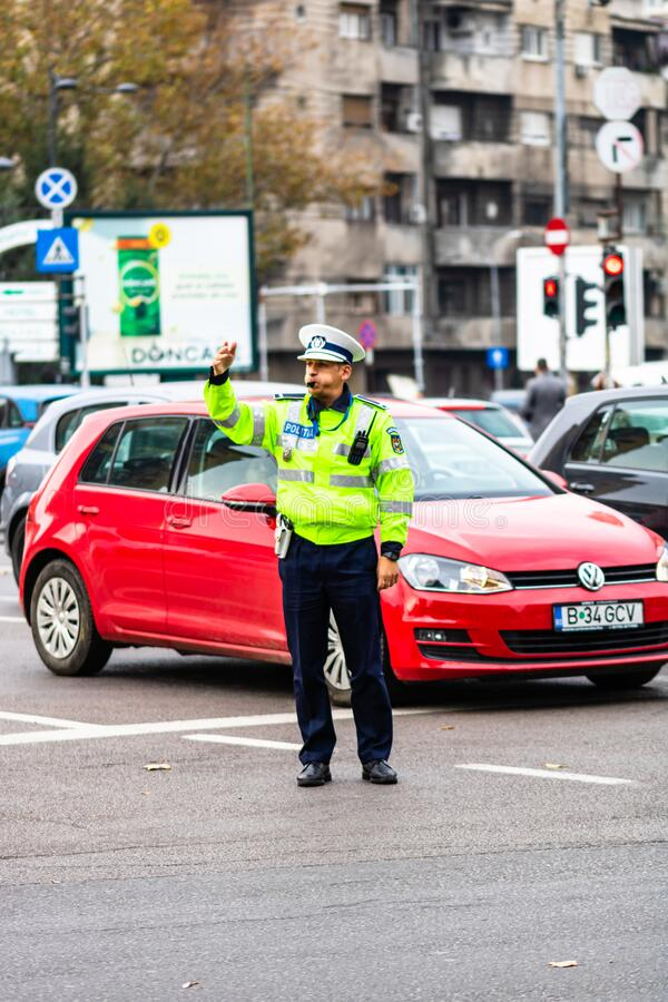 Police agent, Romanian Traffic Police Politia Rutiera directing traffic during the morning rush hour in downtown Bucharest, royalty free stock images