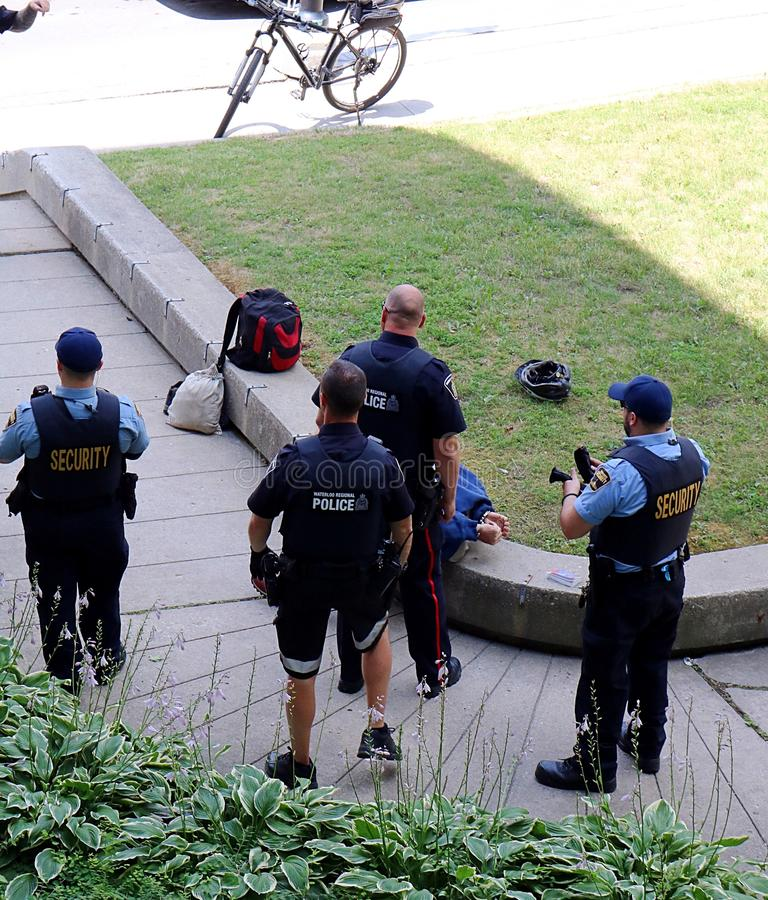 Police arrest man in Kitchener, Waterloo, Ontario. On July 25, 2018 at approximately 1:30 pm, after being detained by security, a man was arrested downtown in a royalty free stock photography