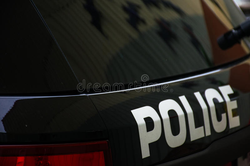 Police Black and white Law Enforcement. The words POLICE on the back of an SUV with a black window and back end of the vehicle stock photography