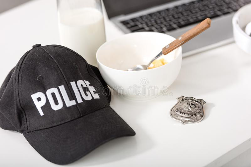 police cap, bowl with cornflakes, police badge and laptop stock images