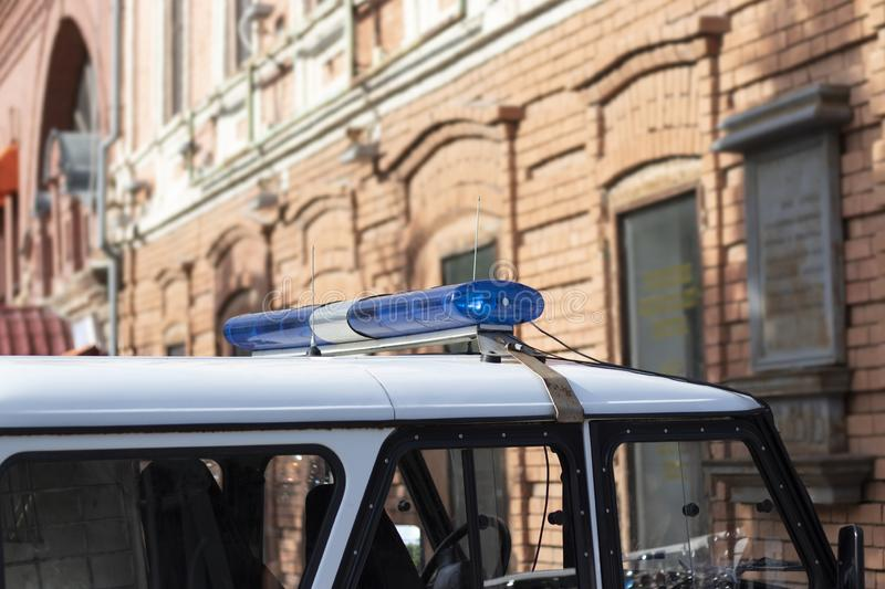 A police car with a blue siren in the afternoon. Patrol car with a flasher royalty free stock image