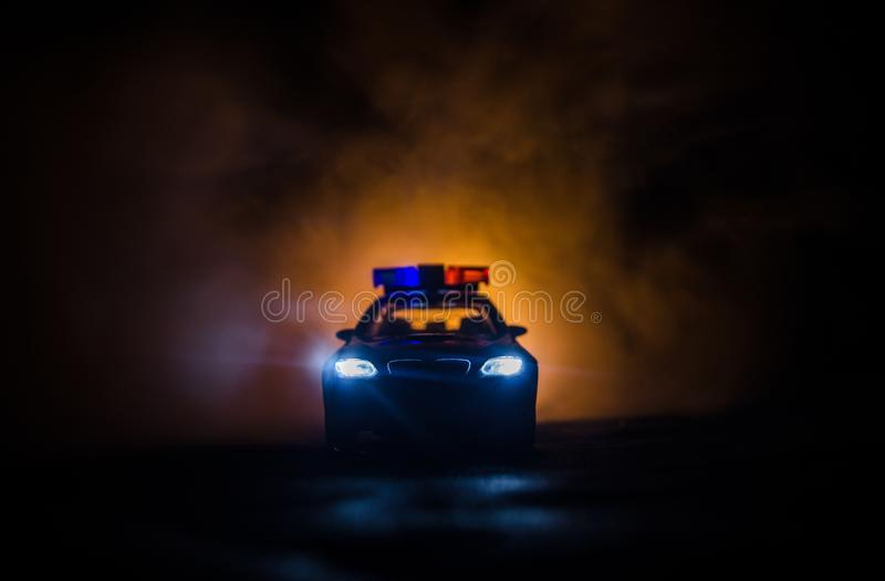 Police car chasing a car at night with fog background. 911 Emergency response police car speeding to scene of crime stock photography
