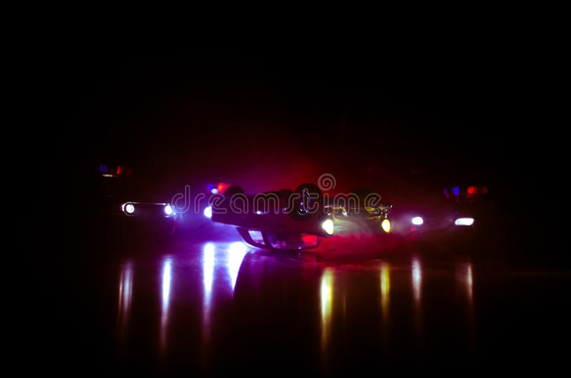 Police car chasing a car at night with fog background. 911 Emergency response police car speeding to scene of crime royalty free stock image