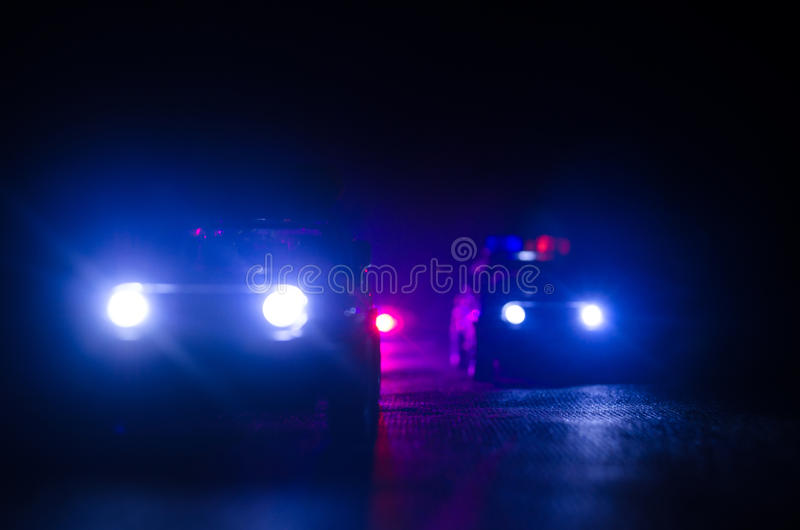 Police car chasing a car at night with fog background. 911 Emergency response police car speeding to scene of crime. stock images