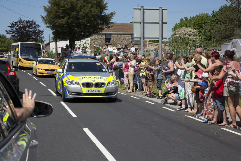 Police car convoy. Olympic torch relay 26 May 2012 Bryncethin Bridgend UK Police car and bus behind in convoy . crowds cheer on the sidline stock photography