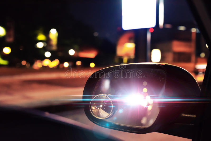 Police car lights reflected on the rearview mirror of a parked c. Photo montage of police car lights reflected on the rearview mirror of a parked car at night stock photo