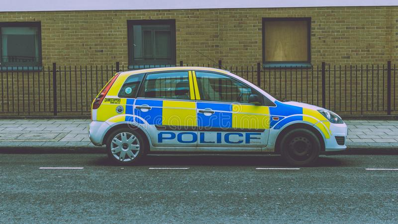 Police Car with missing hubcap parked on a street. Bristol, England - March 16, 2018: Police Car with missing hubcap parked on a street, split toning shallow royalty free stock images