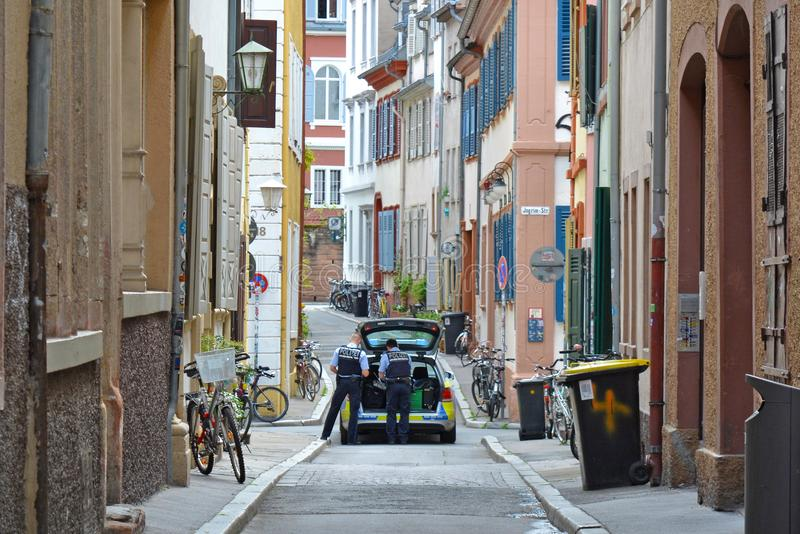 Police car with two officers on patrol in side street of historical city center stock image