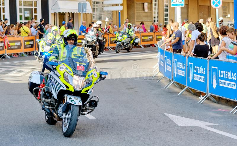 Police control safety of bike riders and spectators during La Vuelta competition. Torrevieja, Spain - August 24, 2019: Police control safety of bike riders and stock photo