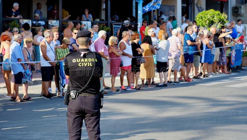 Police control safety of bike riders and spectators during La Vuelta sports competition. Torrevieja, Spain - August 24, 2019: Police control safety of bike stock photography