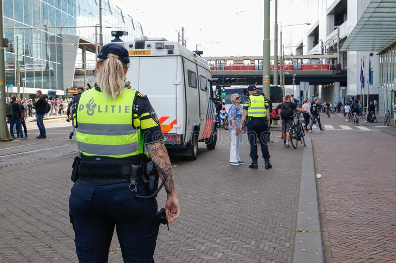 Police cordoning off area to stop people protesting on the streets against lockdown measures by the dutch government in the city royalty free stock photography