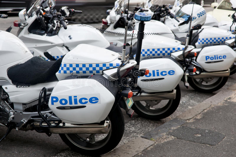 Police cycles lined behind police car. Police motorcycles parked back in to curb, with car at front, showing the signage. Selective focus stock images